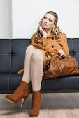 pic of leggins  - woman wearing brown coat with a handbag sitting on sofa - JPG