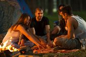 stock photo of daring  - Friends camping in forest together and having fun - JPG