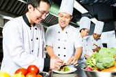 Asian Indonesian chef along with other cooks in restaurant or hotel commercial kitchen cooking, fini