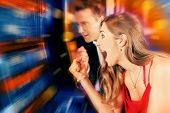 Gambling couple in Casino or amusement arcade on slot machine winning