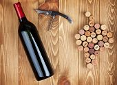 Red wine bottle, corkscrew and grape shaped corks on wooden table background