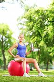 Blond female athlete sitting on pilates ball and holding a water bottle in park