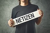 Man Holding White Banner With Word Netizen Printed