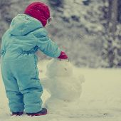 Young Toddler Building A Snow Man