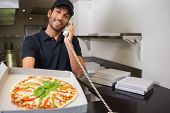 Smiling pizza delivery man taking an order over the phone showing a pizza in a commercial kitchen