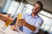 Smiling businessman clinking glass of beer with bartender in a bar