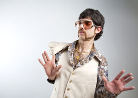 pic of cheeky  - 1970s retro man in a white leisure suite and sunglasses looking surprised - JPG