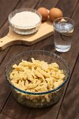 stock photo of glass noodles  - Glass bowl with homemade Hungarian Nokedli or Galuska a type of egg noddle made by cutting the soft dough on a wooden board into boiling water  - JPG