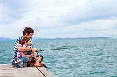 Father and his little son fishing together from wooden jetty