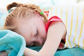 Adorable little girl at beach sleeping on towel tired after traveling