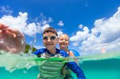 Adorable little girl and cute boy splashing in a tropical ocean water during summer vacation