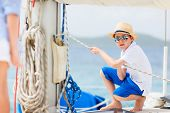 Cute teenage boy enjoying sailing on a luxury catamaran or yacht