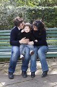 Asian Mother Caucasian Father And Child On A Parkbench