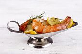 Fresh boiled prawns in a metal oval bowl on wooden background
