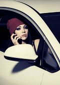 Young fashion woman calling on cell phone in a car
