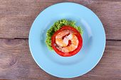 Fresh boiled prawns with pepper on a big blue round plate on wooden background