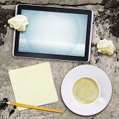 Tablet pc and coffee cup on old concrete surface
