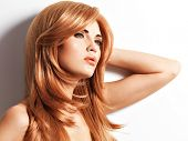 Beautiful woman with long straight red hair. Fashion model over white background