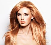Portrait of a beautiful woman with long straight red hair and glamour makeup . Fashion model over wh