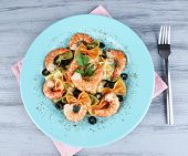 Fresh prawns with coloured macaroni, olives and parsley in a big blue round plate with a fork on woo
