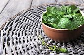Brown round bowl of fresh mint leaves on a stand on wooden table