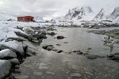 Old Research Station And A Colony Of Penguins Around The Mountains In The Background Of The Antarcti