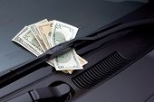 Car expenses symbolized by dollars on a windscreen wiper