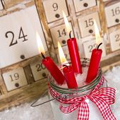 Christmas Eve: Four Red Burning Candles With A Shabby White Advent Calendar Background