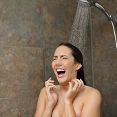 stock photo of water jet  - Disgusted woman screaming in the shower under a cold water jet - JPG