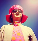 a young boy with a pink wig on and a big tie toned with a retro vintage instagram filter