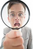 Excited businessman looking through magnifying glass on white background