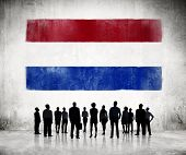 Silhouettes of Business People Looking at the Flag of Netherlands