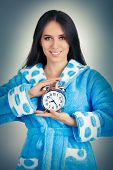 Young Woman in Bathrobe Holding an Alarm Clock