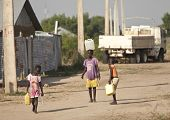 BOR, SOUTH SUDAN-DECEMBER 3 2010: Unidentified children carry containers of water back to their fami