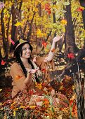 A beautiful Indian teen sitting on the forrest floor happily catching the falling leaves.