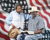 A mature African American cowboy couple reading the Bible with a stars and stripes background.