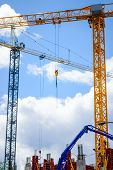 Tall construction cranes at building site