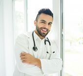 Attractive doctor standing on window and smiling