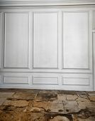 White wooden paneling above a cracked, weathered and worn old flagstone floor in an architectural ba
