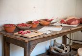 Uncooked red meat in bowls and displayed on a wooden chopping board on a rustic kitchen counter with