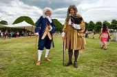 HAMPTON COURT, UK - AUGUST 03, 2014 - Two men dressed in historical Baroque costume during an outdoo