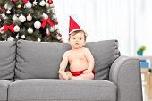 Baby with santa hat and Christmas tree behind her seated on a sofa at home
