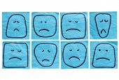 a set of sad and unhappy faces - rough sketches on isolated blue sticky notes