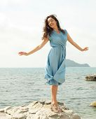 Young happy woman posing near sea, summer vacation