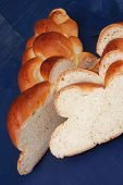 baked product : cuted golden challah on blue wooden table