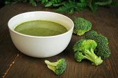 Broccoli soup in a white bowl with fresh vegetables ready to eat