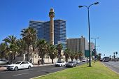 TEL AVIV, ISRAEL - MAY 2, 2014: Spring Tel Aviv promenade. Arab mosque and minaret on the background of high-rise hotel