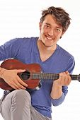 Funny young man playing a little guitar.