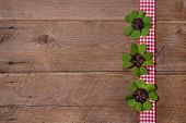 Wooden Background With Red And White Checkered Ribbon And Green Clovers For A Happy New Year