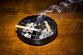 A burning cigar in a classic black ashtray streaming smoking in a dark, moody setting.  The smoke is